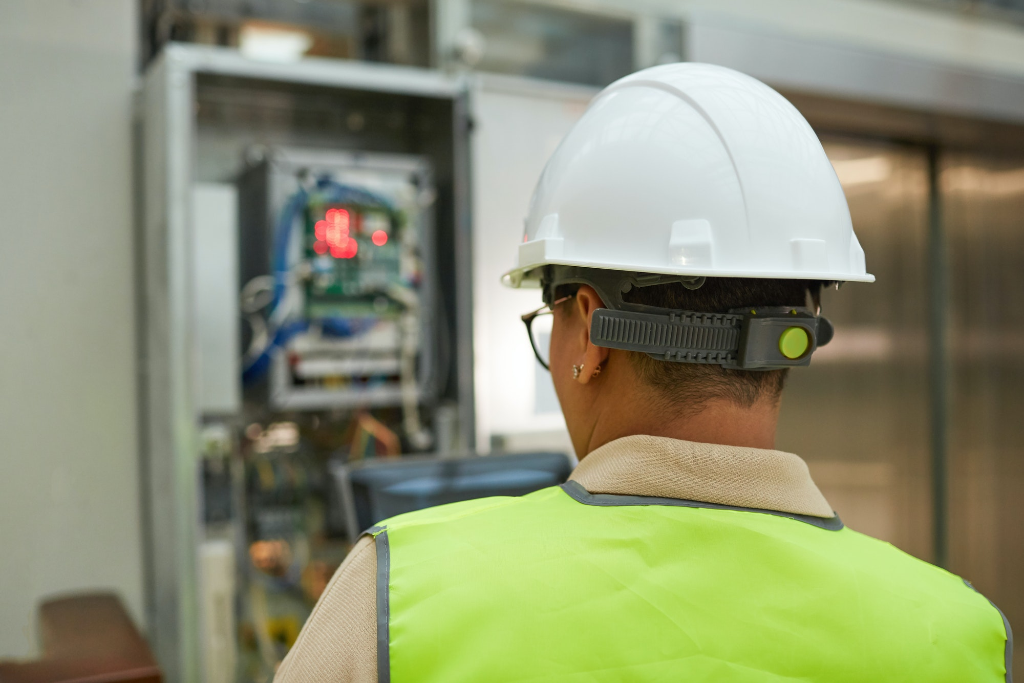 Female Worker Checking Electric Systems Back View
